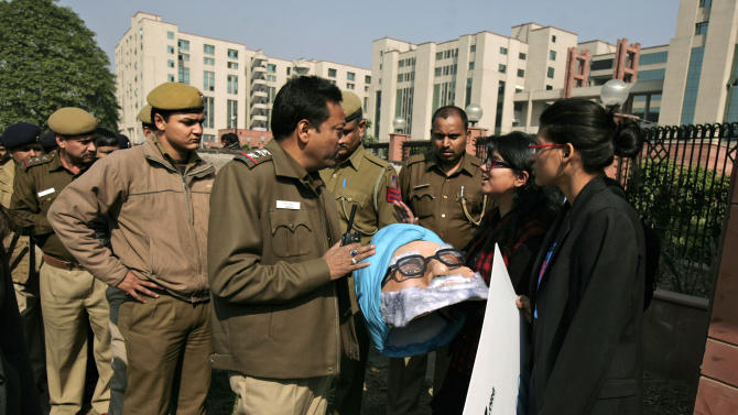 Indian police officials ask activists, holding a mask of Indian Prime Minister Manmohan Singh, to leave as they arrive to protest outside a district court where the accused in the gang rape and murder of a 23-year-old student are undergoing trial, in New Delhi, India, Thursday, Jan. 24, 2013. The trial of the five men charged began in a closed courtroom Thursday with opening arguments by the prosecution lawyers in a special fast-track court set up just weeks ago to handle sexual assault cases. (AP Photo/ Altaf Qadri)