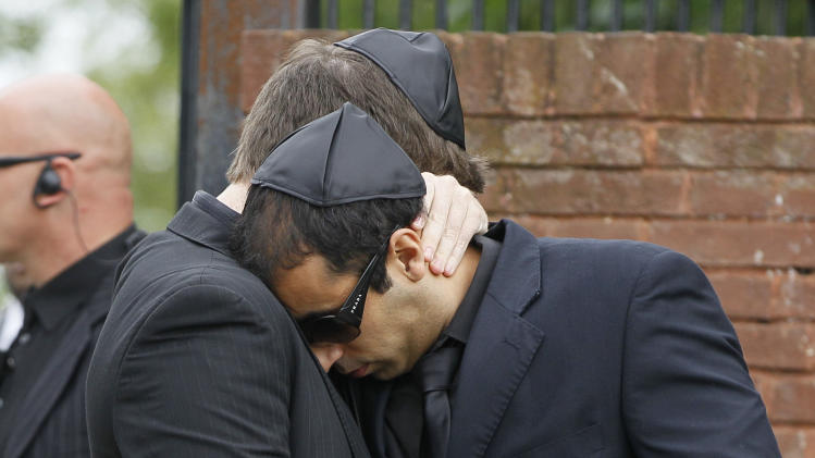Two unidentified mourners embrace as they leave Edgwarebury Cemetery, in London, Tuesday July 26, 2011, after attending the funeral of singer Amy Winehouse.  The soul diva, who had battled alcohol and drug addiction, was found dead Saturday at her London home. She was 27. (AP Photo/Kirsty Wigglesworth)