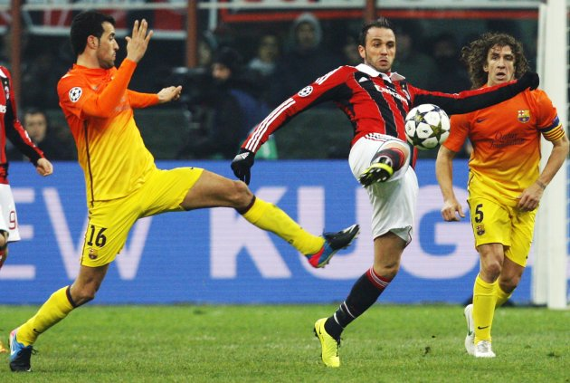 AC Milan's Pazzini challenges Barcelona's Busquets and Puyol during their Champions League soccer match at the San Siro stadium in Milan