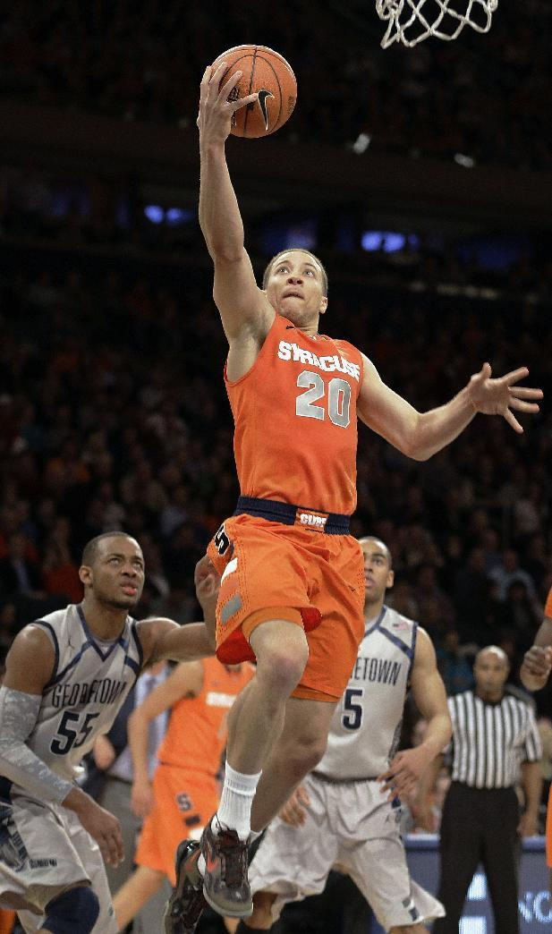 Syracuse's Brandon Triche (20) drives past Georgetown's Jabril Trawick (55) and Markel Starks (5) during the second half of an NCAA college basketball game at the Big East Conference tournament Friday, March 15, 2013, in New York. Syracuse won the game 58-55. (AP Photo/Frank Franklin II)