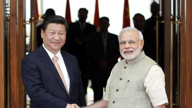 India's PM Modi and China's President Xi shake hands before their meeting in Ahmedabad