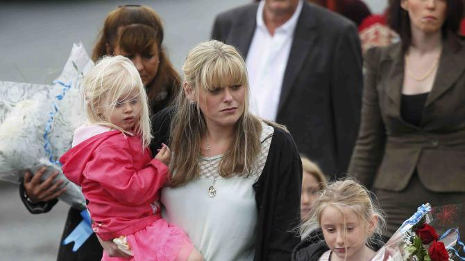 The wife of killed police officer Dave Phillips and their children lead mourners to lay floral tributes where Phillips was struck and killed by a car in Wallasey