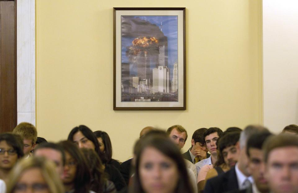 A photo of the burning twin towers of the World Trade Center in New York hangs in the hearing room during the House Homeland Security Committee hearing on Muslim radicalization in the US, Wednesday, July 27, 2011, on Capitol Hill in Washington.  (AP Photo/Evan Vucci)