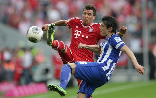 Bayern's Mario Mandzukic of Croatia, left, and Berlin's Nico Schulz challenge for the ball during the German first division Bundesliga soccer match between FC Bayern Munich and Hertha BSC Berlin, in M