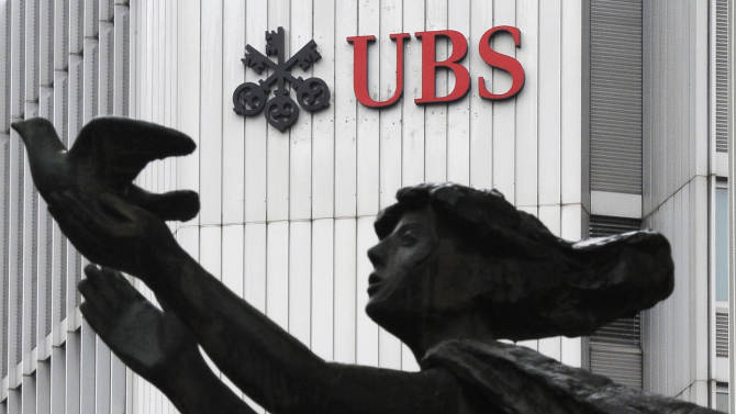 FILE - In this March 19, 2012 file photo the logo of the Swiss bank UBS is pictured behind a statue in Zurich, Switzerland. UBS AG agreed Wednesday, Dec. 19, 2012 to pay some US$1.5 billion in fines to international regulators following a probe into the rigging of a key global interest rate. In admitting to fraud, Switzerland's largest bank became the second bank, after Britain's Barclays PLC, to settle over the rate-rigging scandal. The fine, which will be paid to authorities in the U.S., Britain and Switzerland, also comes just over a week after HSBC PLC agreed to pay nearly US$2 billion for alleged money laundering.  (AP Photo/Keystone, Steffen Schmidt)