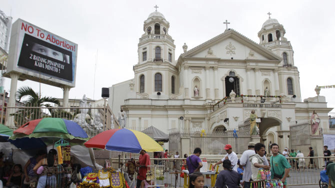 """A """"No to Abortion"""" sign flashes on an electric signboard outside the Roman Catholic Minor Basilica of the Black Nazarene in downtown Manila, Philippines on Thursday, Jan. 3, 2013. Philippine President Benigno Aquino III last month signed the Responsible Parenthood and Reproductive Health Act of 2012. The law that provides state funding for contraceptives for the poor pitted the dominant Roman Catholic Church in an epic battle against the popular Aquino and his followers. (AP Photo/Aaron Favila)"""