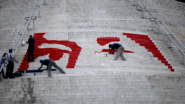 Workers paint a mural that is symbolic of the eyes of Venezuela's late President Hugo Chavez on the stairs at the El Calvario monument in Caracas, Venezuela, Thursday, March 7, 2013.  Chavez died on March 5 after a nearly two-year bout with cancer.  He was 58. (AP Photo/Ariana Cubillos)