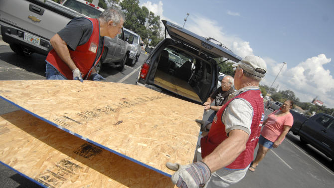 Lowes employees, Robert Tucker, right, and John Lucenti, left, load plywood for Terry King, back, and Ofelia Murphy at Lowes in Fort Walton Beach, Fla., Saturday August 25, 2012. Murphy said they needed some plywood to cover their windows in preparation for Tropical Storm Isaac which is forecasted to make landfall in the Florida Panhandle as a hurricane on Tuesday. (AP Photo/Northwest Florida Daily News, Nick Tomecek)