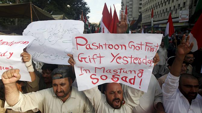 Men hold signs while chanting slogans to condemn an attack on buses in Mastung, a town south of Quetta, during a protest in Karachi, Pakistan