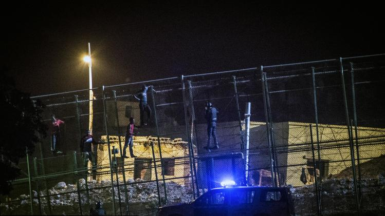 African immigrants sit at the top the border fence, as a Spanish Civil Guard climbs next to them, during an attempt to cross into Spanish territories, between Morocco and Spain's north African enclave of Melilla