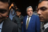 <p>Vijay Mallya, chairman and CEO of India's Kingfisher Airlines, pictured last year in Mumbai, surrounded by bodyguards. The airline's flying licence has been suspended after it failed to satisfy the aviation regulator's concerns about its operations, an official said.</p>