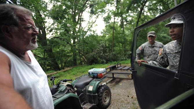 Sgt. Jessica Homeres, right, and Spc. Jeremy Lemaster, with the W.Va. National Guard talk with Raymond Williams near his home after giving him a case of water Thursday, July 5, 2012 in Heaters, W.Va. Residents in the Heaters area have been without power since Friday, June 29, 2012 following a severe storm. (AP Photo/Jeff Gentner)