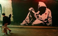 "A man walks past a Banksy graffiti artwork during ""Cans"" graffiti exhibition in London on May 3, 2008. Far from London's beaten tourist track, a group of visitors is staring keenly at the graffiti-covered gates to an abandoned construction site"