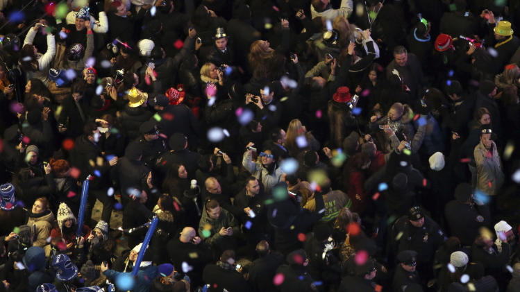 Revelers, center, take pictures as confetti flies over New York's Times Square after the clock strikes midnight during the New Year's Eve celebration as seen from the Marriott Marquis hotel Tuesday, Jan. 1, 2013 in New York.  (AP Photo/Mary Altaffer)