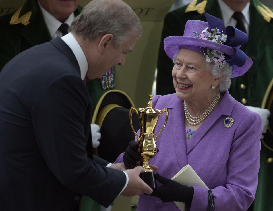 Prince Andrew, the Duke of York presents Britain's Queen Elizabeth II with a trophy after her horse Estimate won the Gold Cup, during day three of the Royal Ascot meeting, at Ascot Racecourse, in Ascot, England, England, Thursday, June 20, 2013. (AP Photo/Alastair Grant)