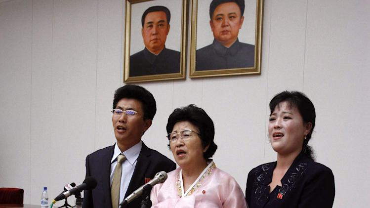 North Korean Pak Jong Suk, center, sings a Korean song titled ìMy Unforgettable Pathî  with her son and daughter-in-law while standing under portraits of former North Korean leaders Kim Il Sung, left, and Kim Jong Il after speaking to reporters at the Peopleís Palace of Culture in Pyongyang, North Korea, on Thursday, June 28, 2012. Pak told local and foreign reporters she was tricked into defecting to South Korea by agents who offered to arrange a reunion with her long-lost father,  but returned home after being disillusioned with life in the South. Her account could not be verified by South Korean officials.   (AP Photo/Kim Kwang Hyon)