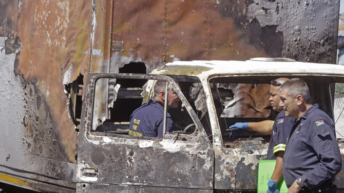 South African Police forensic team members look for leads in a burnt out truck near  Cape Town, South Africa, Thursday, Oct 11, 2012. South African truck drivers are on strike over wages for the past three week's with around twenty five trucks being burnt around Cape Town city resulting in the death of two drivers  after there trucks were set alight. (AP Photo/Schalk van Zuydam)