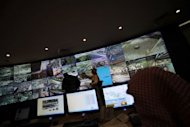 Saudi security personnel monitor the screens as they follow the hajj pilgrimage from the control room on the second day of Eid al-Adha, in Mina