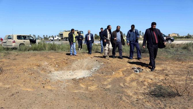 Members of the airport security and civil aviation officials examine the scene after an airstrike hit Tripoli's Maitiga airport