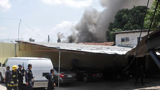 Police and firefighters work as smoke rises from a penitentiary, behind, in San Pedro Sula, Honduras, Thursday March 29, 2012.  As many as 18 people died during an uprising by armed inmates at the prison Thursday, one of them decapitated and the others killed by a fire started by the rioters, authorities said. (AP Photo)