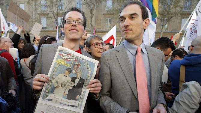 Pro gay marriage activists pose after French lawmakers legalized same-sex marriage, Tuesday, April 23, 2013 in Paris. Lawmakers legalized same-sex marriage after months of bruising debate and street protests that brought hundreds of thousands to Paris. Tuesday's 331-225 vote came in the Socialist majority National Assembly. France's justice minister, Christiane Taubira, said the first weddings could be as soon as June. (AP Photo/Francois Mori)