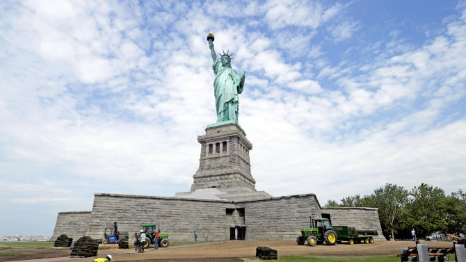 In this June 26, 2013 photo provided by the National Park Service, workers on Liberty Island install sod around the national monument which is set to re-open on the 4th of July, in New York. Months after railings broke, docks and paving stones were torn up and buildings were flooded by Superstorm Sandy, the Statue of Liberty will finally welcome visitors again. (AP Photo/National Park Service,