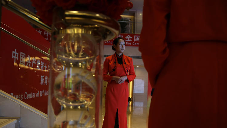 A hostess waits for journalists to arrive for a press conference held as part of the 18th Communist Party Congress in Beijing, China, Saturday, Nov. 10, 2012. (AP Photo/Ng Han Guan)