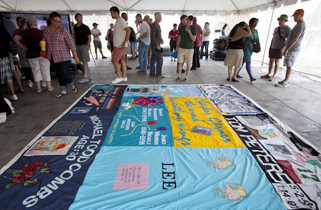 People gather around a section of the AIDS Memorial Quilt, on the National Mall in Washington, Saturday, July 21, 2012. The full quilt's display on the Mall was delayed due to rain. (AP Photo/Jacquelyn Martin)