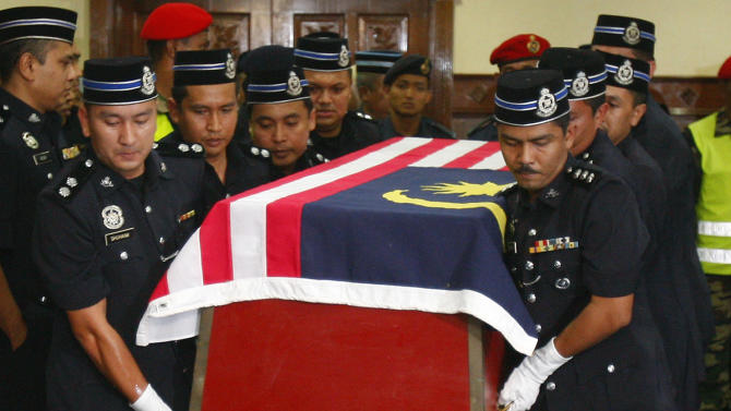 Malaysian police officers carry the coffin of a policeman who was killed in an ambush in Semporna, Malaysia, after its arrival at the Royal Malaysian Air Force base in Subang, near Kuala Lumpur, Malaysia, Monday, March 4, 2013. Malaysia sent hundreds of soldiers to a Borneo state on Monday to help neutralize armed Filipino intruders who have killed eight police officers in the country's bloodiest security emergency in years. (AP Photo/Lai Seng Sin)