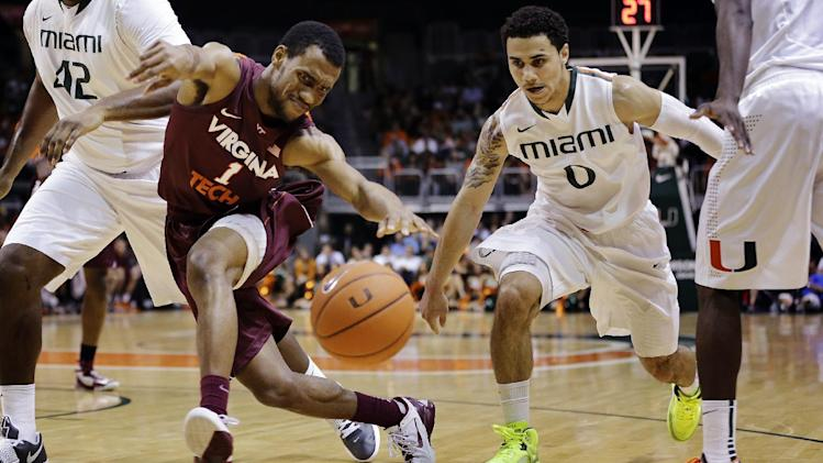 Virginia Tech's Robert Brown (1) and Miami's Shane Larkin (0) go for a loose ball during the first half of an NCAA college basketball game in Coral Gables, Fla., Wednesday, Feb. 27, 2013. (AP Photo/J Pat Carter)