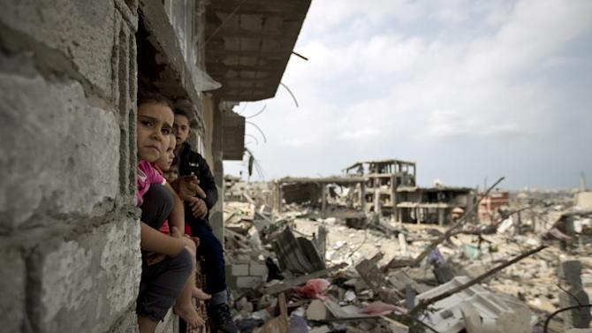 Palestinian children sit in the window of a partially destroyed building in al-Tufah, east of Gaza City on October 11, 2014