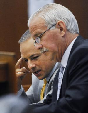 Detroit Police officer Joseph Weekley, left, and his attorney Steve Fishman confer during a break in the proceedings at the Frank Murphy Hall of Justice in Detroit Wednesday, June 5, 2013. Weekley is on trial for involuntary manslaughter in the death of Aiyana Stanley-Jones, 7, during a police raid. (AP Photo/Detroit News, Daniel Mears) DETROIT FREE PRESS OUT; HUFFINGTON POST OUT