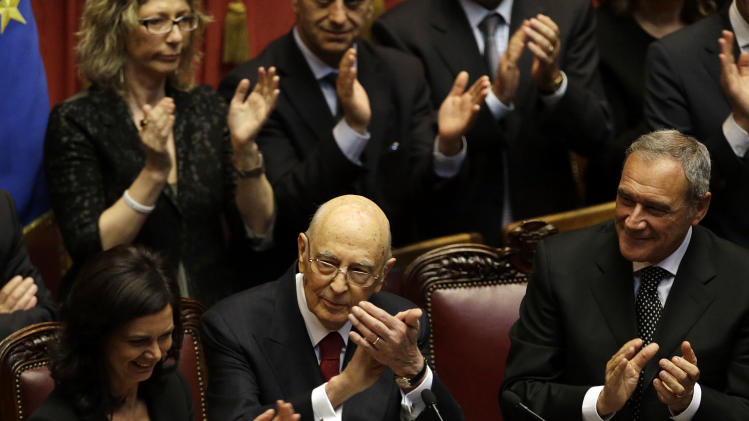 Italian President Giorgio Napolitano, flanked by the chairman of the Lower House Laura Boldrini, left, and  the chairman of the Senate Pietro Grasso, right, joins the applause of lawmakers after delivering his speech at the lower chamber in Rome, Monday, April 22, 2013. President Giorgio Napolitano headed Monday into his unprecedented second term with the daunting task of trying to find a candidate who can form a government two months after national elections left Italy with no clear winner and an increasingly discredited political class. (AP Photo/Gregorio Borgia)