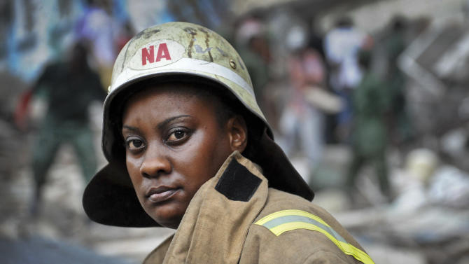 A rescuer looks across as she works amongst the rubble of a collapsed building in downtown Dar es Salaam, Tanzania Friday, March 29, 2013. A Tanzanian police official says the multi-storey building was in the final stages of its construction and most of the people caught up in the collapse were passing by. (AP Photo/Khalfan Said)