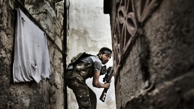 In this photo provided on Friday Feb. 15, 2013 by World Press Photo, the 2nd prize Spot News Stories by Fabio Bucciarelli, Italy, for Agence France-Presse, a Free Syrian Army (FSA) fighter takes position during the clashes against Syrian government forces in Sulemain Halabi district in Aleppo, Syria, Oct. 10, 2012. (AP Photo/Fabio Bucciarelli, Agence France-Presse)