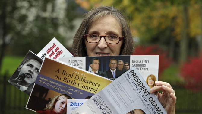 """In this photo taken Oct. 19, 2012,  Jean Gianfagna displays some of the political mailers her family receives at her home in Westlake, Ohio. Gianfagna says her family is """"deluged"""" and sometimes gets four of the same piece at a time _ her husband and two grown kids all get their own. (AP Photo/Mark Duncan)"""