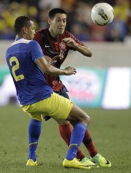 United States midfielder Clint Dempsey, right, and Ecuador defender Eduardo Morante compete for the ball in the first half of an international soccer friendly game, Tuesday, Oct. 11, 2011, in Harrison, N.J. (AP Photo/Julio Cortez)