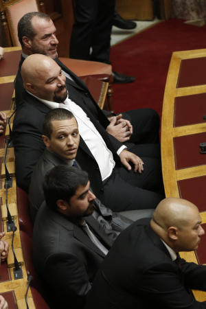 Lawmakers of the extreme far-right Golden Dawn from bottom to top, Giorgos Germenis, Artemios Matheopoulos, Ilias Kasidiaris, Ilias Panayiotaros, and Nikos Michos attend a blessing ceremony for the upcoming parliamentary season inside the parliament hall, in Athens, Monday, Oct. 7, 2013. Greek politicians arrived in Parliament on Monday for the religious ceremony, as Golden Dawn leader Nikos Michaloliakos and two more lawmakers remained jailed pending trial on charges of running a criminal organization. Kassidiaris, Panayiotaros and Michos face similar charges but have been released from police custody pending trial. (AP Photo/Petros Giannakouris)