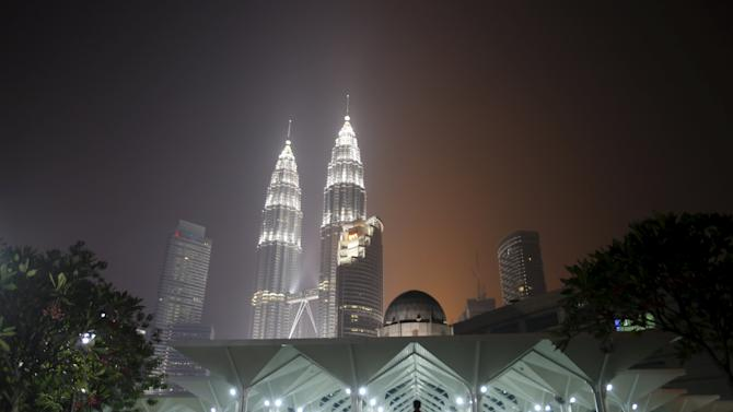 File photo of man arriving for prayers at mosque at foot of haze-covered Malaysian landmark Petronas Twin Towers in Kuala Lumpur