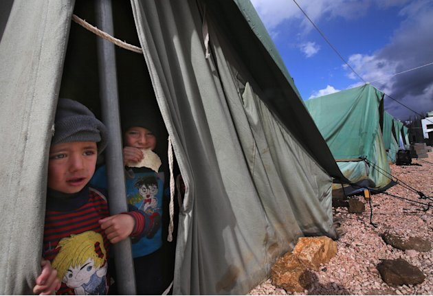 Syrian refugee boys look outside their tent, at a temporary refugee camp in the eastern Lebanese town of Marj near the border with Syria, Lebanon, Monday, Jan. 7, 2013. Syrian refugees worked on reinf