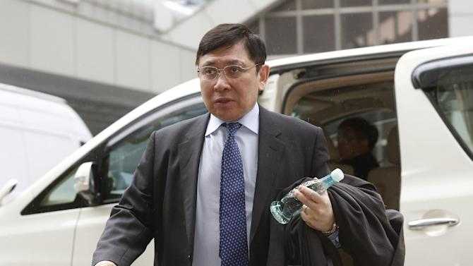 Raymond Kwok, co-chairman of developer Sun Hung Kai Properties, arrives at the High Court in Hong Kong, Friday, Dec. 19, 2014. A Hong Kong jury found Raymond's billionaire elder brother Thomas Kwok, co-chairman of the developer company, and former top government official Rafael Hui guilty of corruption after a high profile trial. Raymond, also a billionaire, was found not guilty. Thomas Kwok was Friday convicted of conspiracy for making HK$8.5 million (US$1.1 million) of payments to Hui. (AP Photo/Kin Cheung)