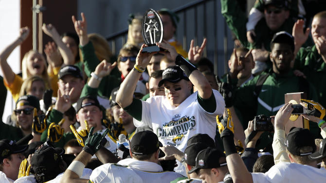 North Dakota State quarterback Brock Jensen holds up the most valuable playyer trophy as he stands surrounded by teammates after their 39-13 win in FCS Championship NCAA college football game against Sam Houston State, Saturday, Jan. 5, 2013, in Frisco, Texas. (AP Photo/Tony Gutierrez)