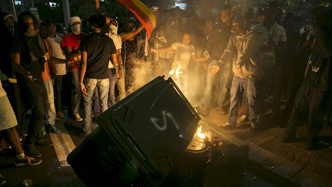 Protesters, whom are mainly Israeli Jews of Ethiopian origin, stand next to a garbage bin they set on fire at Rabin Square during a demonstration against what they say is police racism and brutality