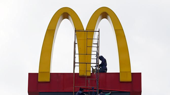 Workers repair the logo on a McDonald's sign in Paranaque, Metro Manila