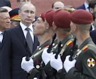 Russian President Vladimir Putin watches soldiers march past during a ceremony at the Tomb of Unknown Soldier on the eve of the Victory Day celebrations in Moscow