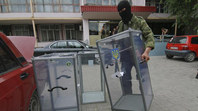 A Pro-Russian activist carries a ballot box away from a polling station preparing to smash it, in Donetsk, Ukraine, Friday, May 23, 2014. Ukraine's acting government has admitted that authorities will not be able to organize the voting in parts of eastern Ukraine, overrun by pro-Russian insurgents. (AP Photo/Photomig)