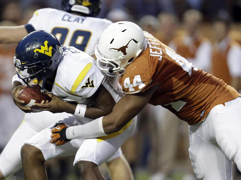 West Virginia quarterback Geno Smith, left, is sacked by Texas defender Jackson Jeffcoat (44) during the second quarter of an NCAA college football game on Saturday, Oct. 6, 2012, in Austin, Texas. (AP Photo/Eric Gay)