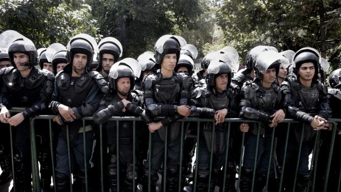 """Iranian police officers stand guard in front of the Swiss Embassy in Tehran, which represents US interests in Iran, during a demonstration against a film ridiculing Islam's Prophet Muhammad, Thursday, Sept. 13, 2012. The search for those behind the provocative anti-Muslim film led Wednesday to a California Coptic Christian convicted of financial crimes who acknowledged his role in managing and providing logistics for the production. Nakoula Basseley Nakoula, 55, told The Associated Press in an interview outside Los Angeles that he was manager for the company that produced """"Innocence of Muslims,"""" which mocked Muslims and the prophet Mohammed and was implicated in inflaming mobs that attacked U.S. missions in Egypt and Libya. (AP Photo/Vahid Salemi)"""