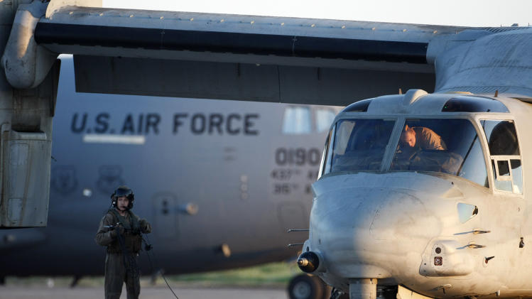 US navy personnel seen next to a US  MV-22 Osprey vertical take off and lift aircraft, right, and a C-5 Galaxy aircraft in the Sigonella airbase, Sicily, Thursday, March 24, 2011.  (AP Photo/Andrew Medichini)