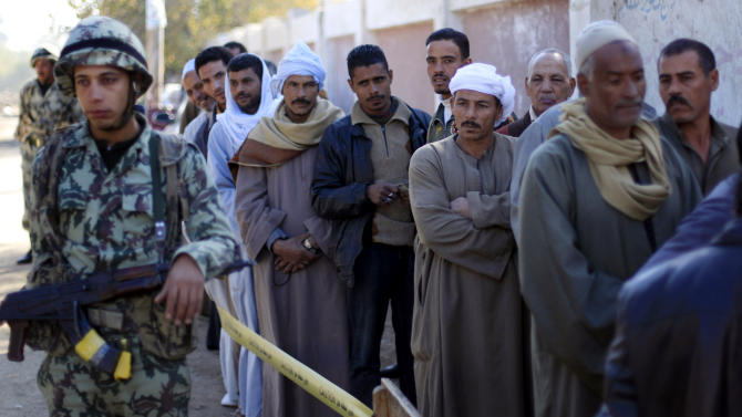 Egyptians line up outside a polling station wait their turn to cast their votes during the second round of a referendum on a disputed constitution drafted by Islamist supporters of President Mohammed Morsi in Fayoum, about 100 kilometers (62 miles) south of Cairo, Egypt, Saturday, Dec. 22, 2012.(AP Photo/Khalil Hamra)